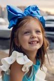 一个小女孩的画象与蓝色弓的三年在她的头,微笑着 库存照片