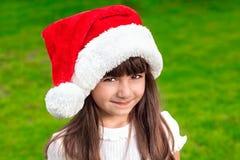 一个小女孩的画象圣诞节帽子的在背景  免版税图库摄影