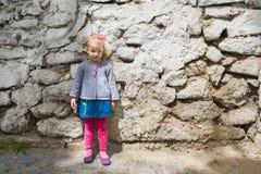 一个小女孩的画象在街道上的,严肃,反对老墙壁背景 库存照片