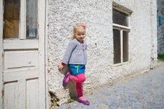一个小女孩的画象在街道上的,严肃,反对老墙壁背景 免版税库存照片