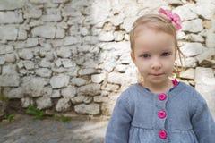 一个小女孩的画象在街道上的,严肃,接近,反对老墙壁背景 库存图片