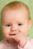 一个小女孩的画象有她的手指的在她的嘴 免版税库存照片