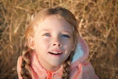 一个小女孩的画象有蓝眼睛和猪尾的 免版税库存照片
