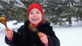 一个小女孩皮大衣的和在俄国样式的一条红色围巾的在木匙子使用 股票视频
