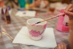 一个小女孩装饰在桃红色颜色的一个杯子 库存图片