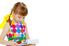 一个小女孩读小册子 免版税库存照片