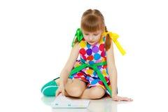 一个小女孩读小册子 免版税库存图片