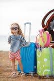 一个小女孩继续在一辆红色汽车的一次旅途 库存照片