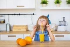 一个小女孩滑稽的饮料的画象在桌上的新鲜的汁液 图库摄影