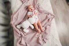 一个小婴孩在一张床放置用玩具兔子并且微笑 免版税图库摄影
