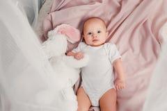 一个小婴孩在一张床放置用玩具兔子并且微笑 库存照片