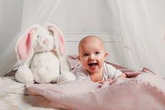 一个小婴孩在一张床放置用玩具兔子并且微笑 免版税库存照片