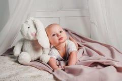 一个小婴孩在一张床放置用玩具兔子并且微笑 库存图片