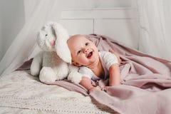 一个小婴孩在一张床放置用玩具兔子并且微笑 图库摄影