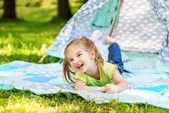 一个小学龄前儿童在毯子和笑说谎 夏天 库存照片
