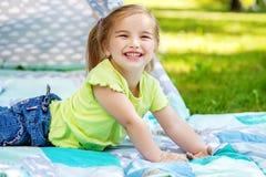 一个小学龄前孩子在一条毯子说谎在公园 Summe 库存图片