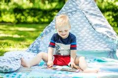 一个小孩在公园笑并且读一本书 男孩幼儿园 免版税库存照片
