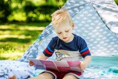 一个小孩在公园读一本书 男孩幼儿园 浓缩 免版税库存照片