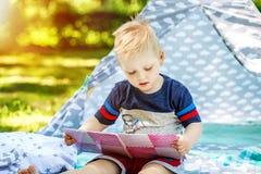 一个小孩在公园读一本书 男孩幼儿园 concep 库存图片