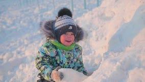 一个小孩子充当有雪的一个冬天公园 日晴朗的冬天 乐趣和比赛在新鲜空气 免版税图库摄影