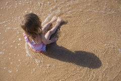 一个小孩子坐海滩 在视图之上 库存图片