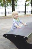 一个小孩子学会在长凳,小孩附近走 免版税图库摄影