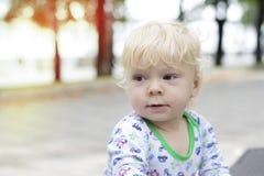 一个小孩子学会在长凳,小孩附近走 库存图片
