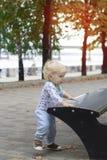 一个小孩子学会在长凳,小孩附近走 免版税库存照片