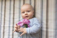 一个小孩子拿着一朵桃红色牡丹花 免版税库存图片