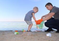 一个小孩子收集在海滩的垃圾 他的爸爸在哪里指向他的手指投掷垃圾 父母教孩子洁净 免版税库存照片