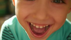 一个小孩子显示情感:笑声,幸福,喜悦,微笑 儿童的面孔的特写镜头:笑的嘴和牙 股票视频