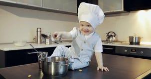 一个小孩子烹调敞篷与在金属平底深锅的一把匙子混合曲奇饼 股票视频