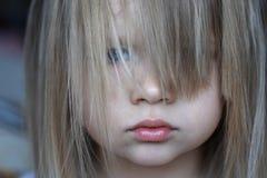 一个小微笑的女孩的画象有她的头发的宽松在她的面孔 免版税库存图片