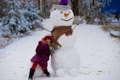 一个小快乐的女孩在大真正的滑稽的雪人附近坐 图库摄影