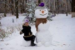 一个小快乐的女孩在大真正的滑稽的雪人附近坐 免版税库存图片