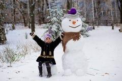 一个小快乐的女孩在大真正的滑稽的雪人附近坐 免版税库存照片