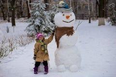一个小快乐的女孩在大真正的滑稽的雪人附近坐 库存照片