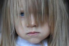 一个小恼怒的女孩的画象有她的头发的在她的面孔疏松 库存照片