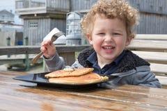 一个小愉快的男孩吃着薄煎饼外面 库存图片