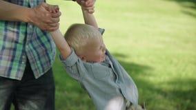 一个小愉快的男孩的画象,当使用与他的爸爸在公园时 摇摆他的小男孩慢动作充分的HD的爸爸 影视素材