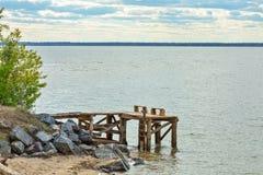 一个小暂时木码头和板条长凳在岸的 库存图片