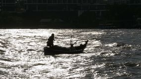 一个小木渔船的剪影有移动由海的渔夫的 泰国 聚会所 影视素材
