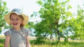一个小欧洲女孩吹从一个白色蒲公英的蓬松种子 股票录像