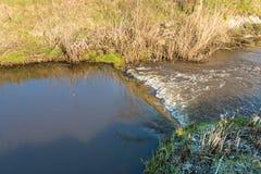 一个小测流堰的特写镜头在一条狭窄的小河的 库存图片