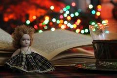 一个小玩偶、一本开放书和一杯茶在一个灼烧的壁炉和圣诞灯,诗歌选的背景的 库存照片
