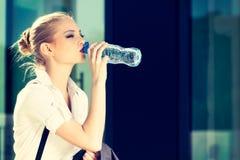 从一个小瓶的年轻女商人饮用水 免版税库存照片
