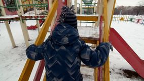 一个小男婴在冬时的操场到处乱跑的HD 影视素材