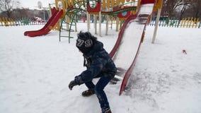 一个小男婴在冬时的操场滑下来的HD 股票录像