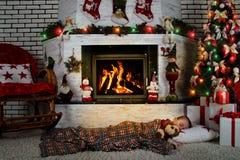 一个小男孩与玩具狗睡觉在一棵圣诞树下在有一个灼烧的壁炉的一间屋子里 免版税图库摄影