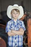 一个小男孩佩带的牛仔帽的画象,当站立与胳膊横渡了反对机器时 库存图片